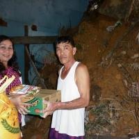 Một người dân nhận quà cứu trợ trong lúc còn đang dọn mớ xà bần ngổn ngang khi đổ vách do lỡ núi
